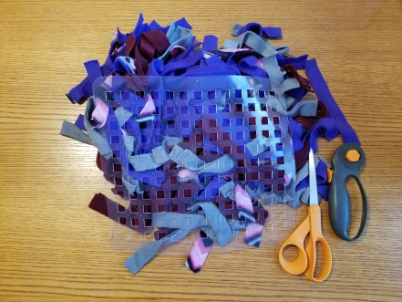 Fleece strips, dish mat, scissors, and rotary cutter.