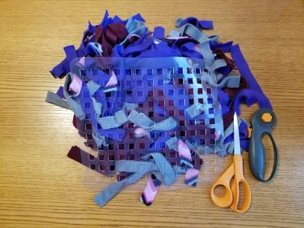 Fleece strips, dish mat, scissors, and rotary cutter.
