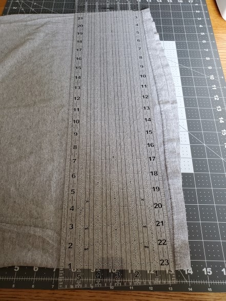 A gray t-shirt layed out on a cutting mat with a clear ruler on top of it.