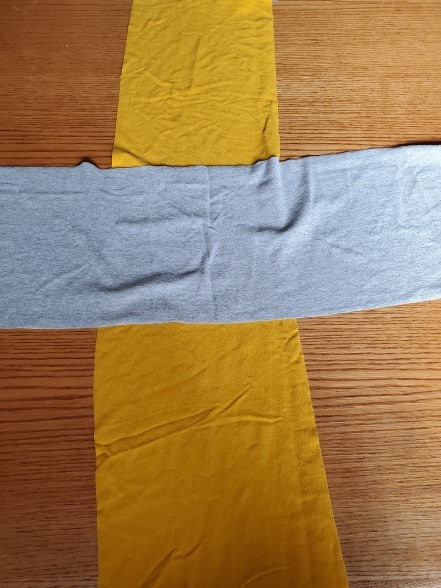 A wide gray t-shirt strip laid across a wide, gold t-shirt strip.
