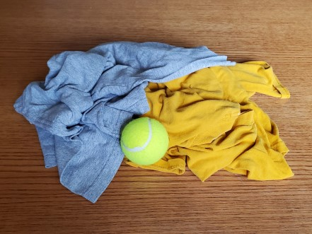 A gray t-shirt and a gold t-shirt with a tennis ball.