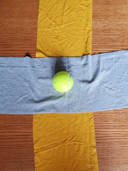 A wide gray t-shirt strip laid across a wide, gold t-shirt strip with a tennis ball on top in the middle.